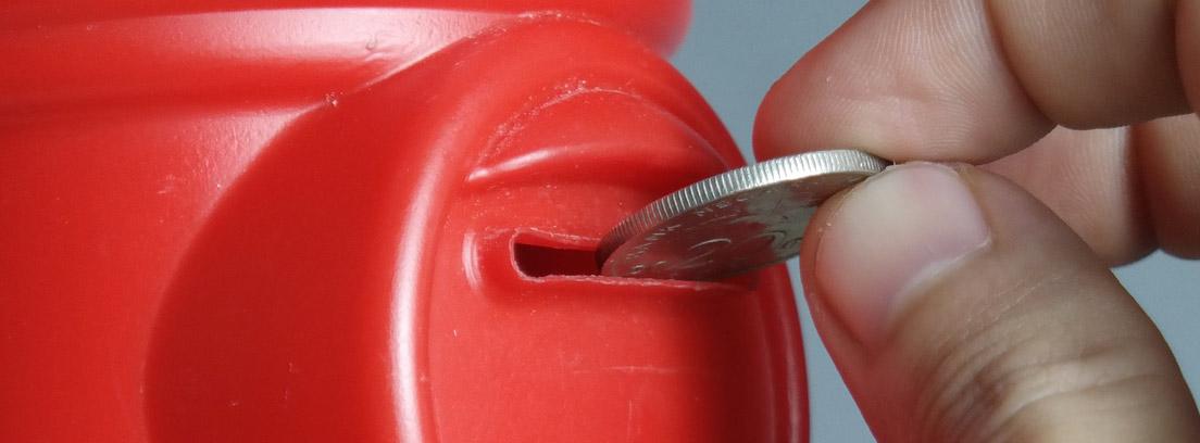 Mano metiendo una moneda en una hucha roja