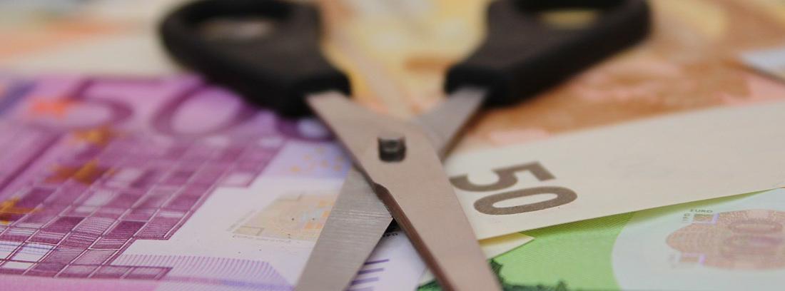 Tijera abierta sobre billetes y monedas de Euro
