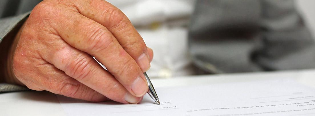 Mano de hombre mayor firmando