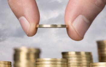 Mano depositando una moneda sobre una columna de monedas