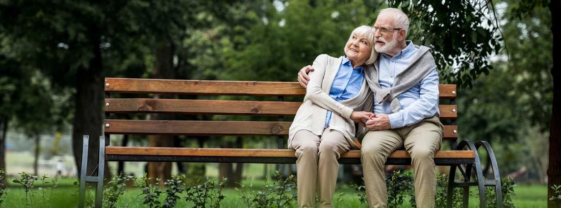 Hombre y mujer con pelo canoso sentados en un banco abrazados con gesto feliz