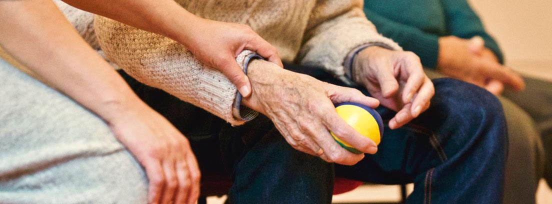Persona mayor sentada con una pequeña pelota en la mano