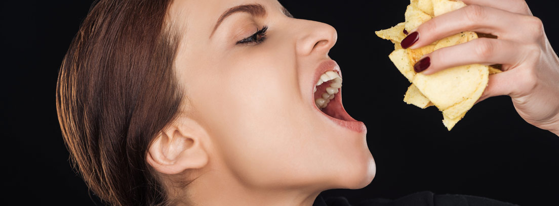Mujer comiendo un puñado de patatas fritas