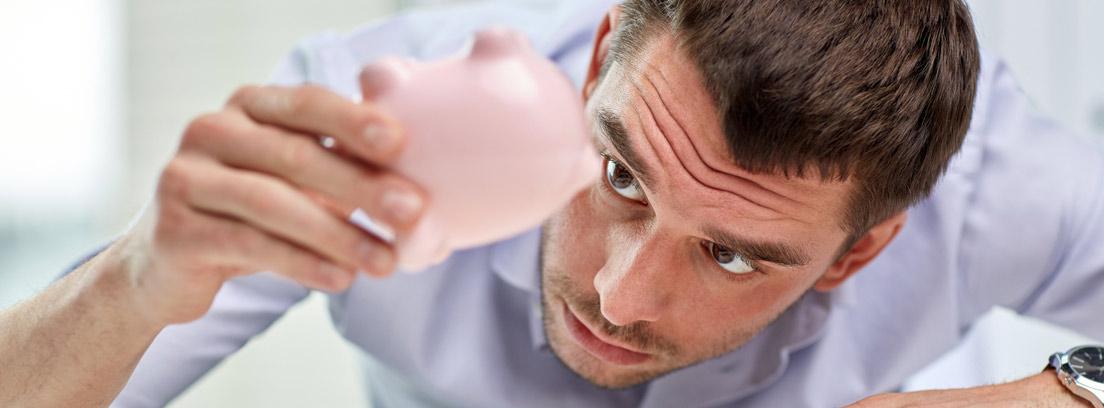 Hombre mirando una hucha de cerdo