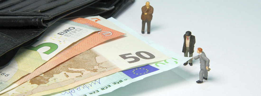 Pequeños muñecos al lado de billetes de euro saliendo de una cartera