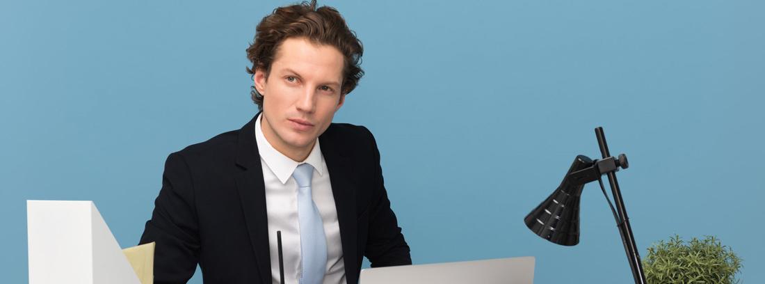 Hombre joven con gesto pensativo en mesa de trabajo con ordenador