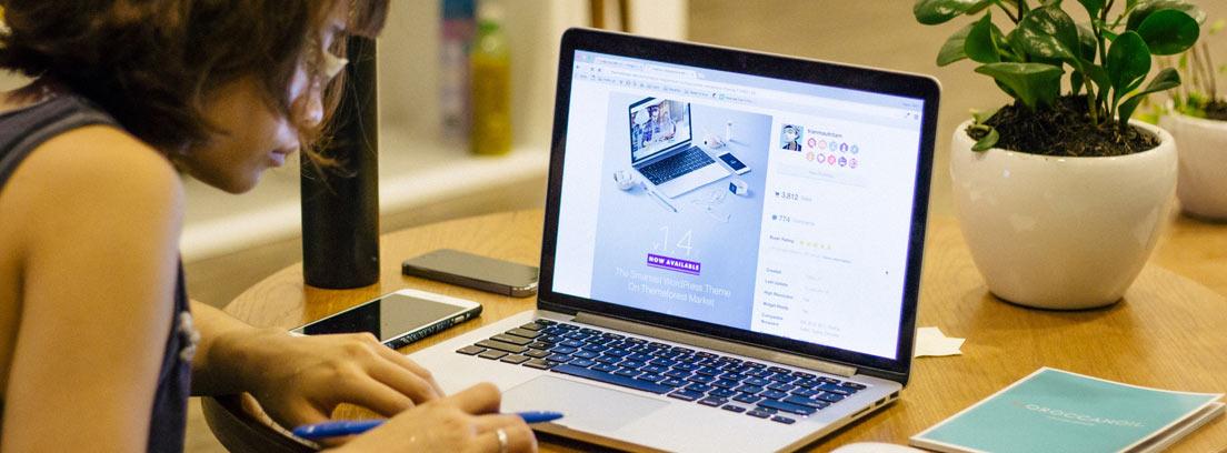 Mujer delante del ordenador portátil tomando notas