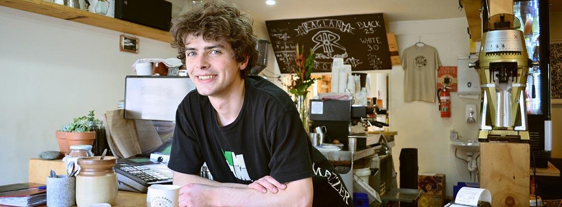 Joven sonriente tras la barra de una cafetería