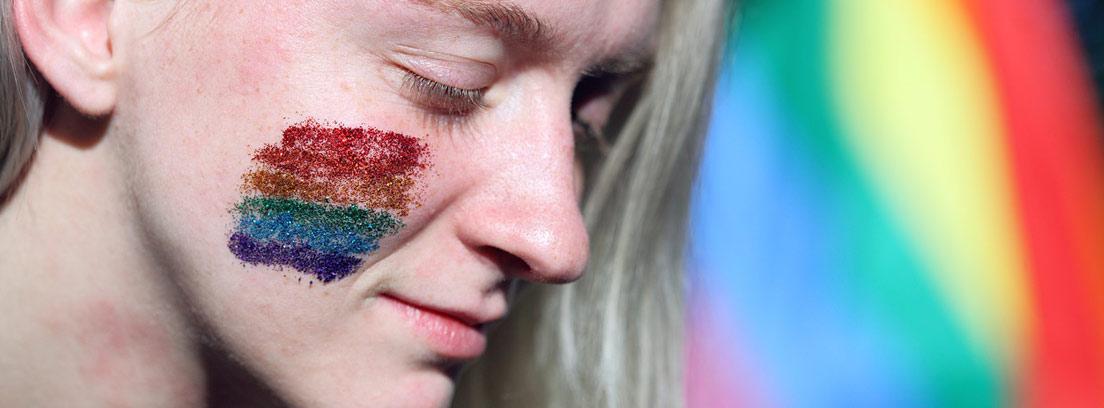joven con la bandera LGTB pintada en la cara