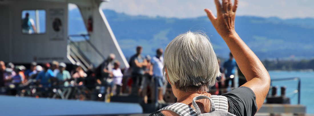 Mujer mayor con mochila saludando