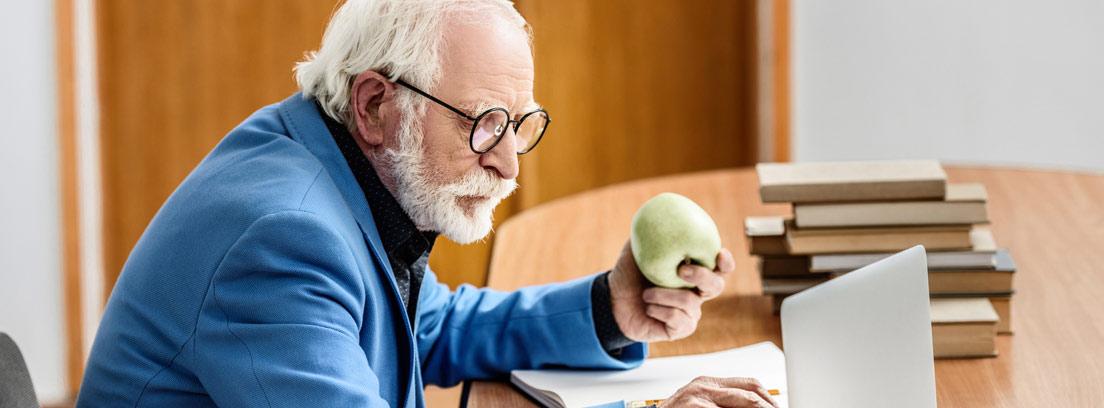 Hombre mayor estudiando con su ordenador y unos libros