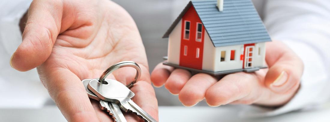 Mano entregando las llaves de una vivienda mientras en la otra sujeta una casa de juguete