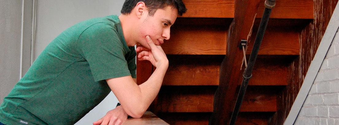 Hombre apoyado en una barandilla de madera pensando