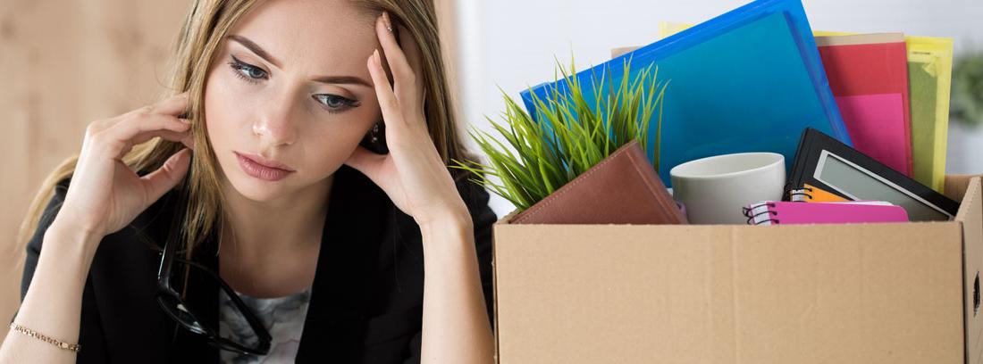 Mujer apoyando la cabeza en una mano con gesto triste al lado de una caja llena de cosas