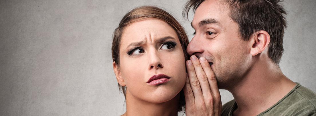 Hombre contando un secreto a una mujer con gesto de incredulidad