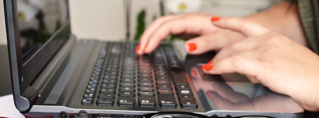 Manos de mujer tecleando un ordenador junto a unos papeles, un boli y unas gafas