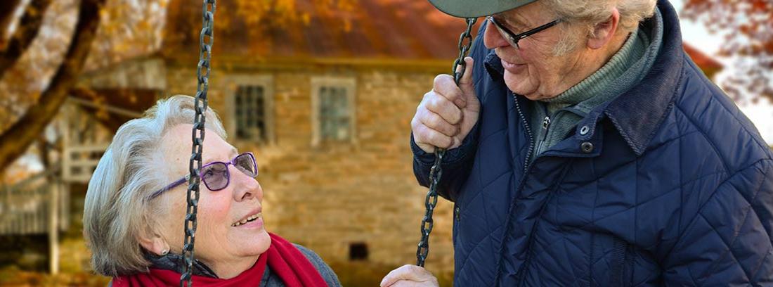 Dos ancianos se miran y sonríen en unos columpios