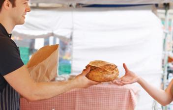 Mujer en un puesto comprando pan, uno de los productos a los que se aplica el IVA superreducido