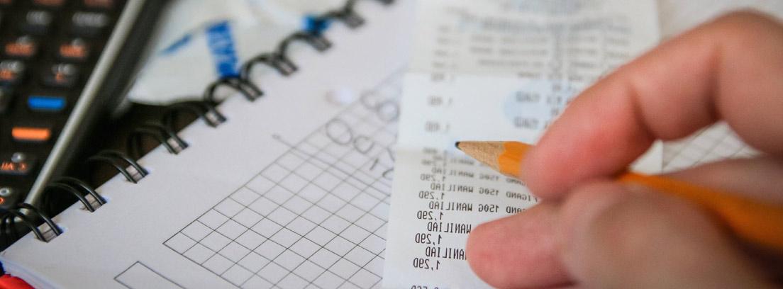 Primer plano de una mano con un lápiz sobre cuadernos, calculadora y un ticket de compra