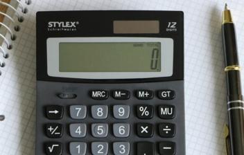 Calculadora sobre cuaderno de cuadros y junto a bolígrafo