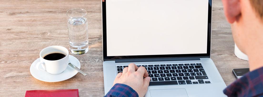 Persona de espaldas con una mano sobre ordenador portátil