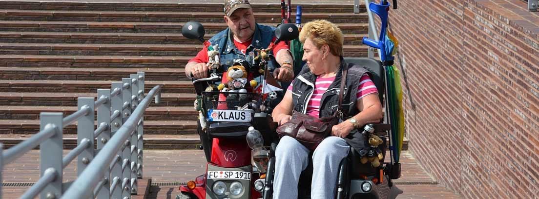 Hombre y mujer en silla de ruedas junto a escaleras