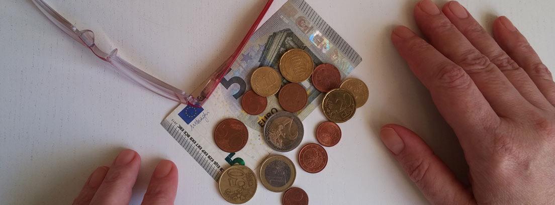 Vista cenital de unas manos sobre una mesa junto a unas monedas y billetes y unas gafas