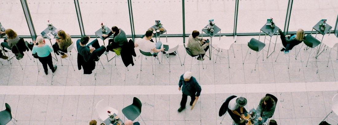 Vista aérea de un espacio con mesas y sillas y personas sentadas y andando