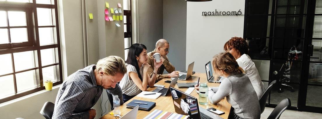 Personas de diferentes edades con ordenadores y papeles en una mesa