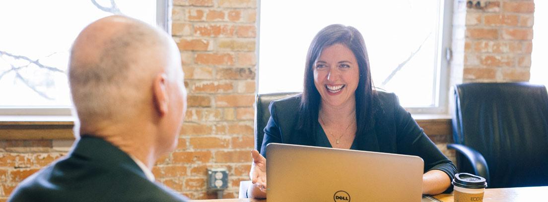Mujer joven sonriente con ordenador y frente a hombre con pelo blanco de espaldas