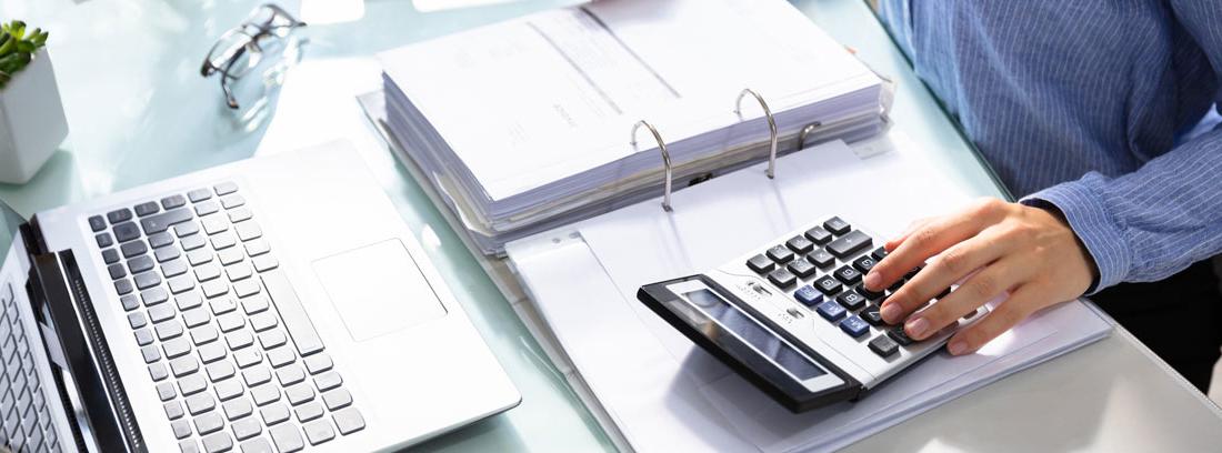 Mujer en una mesa con un ordenador, calculadora y un archivador de documentos