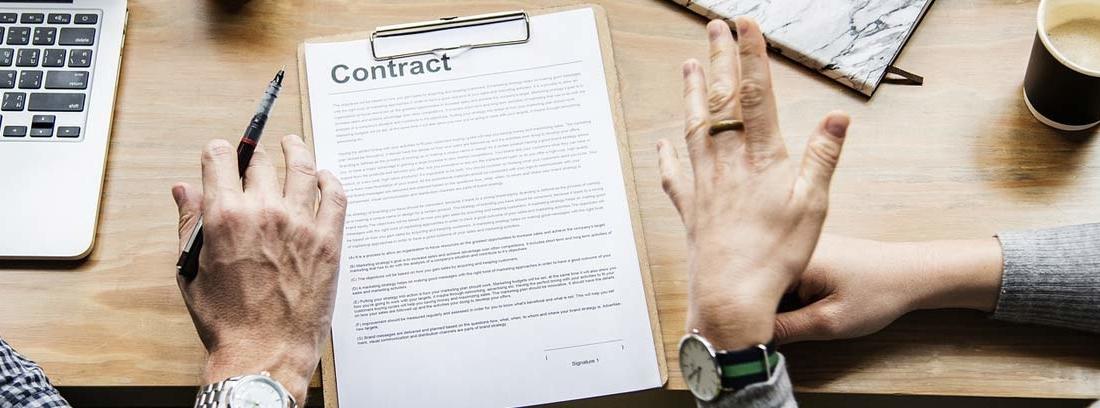 Manos de dos personas sentadas a una mesa con un documento delante