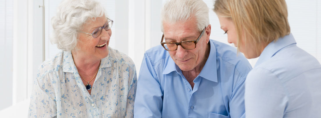 Hombre y mujer con pelo blanco y gafas en un sillón frente a una mujer joven