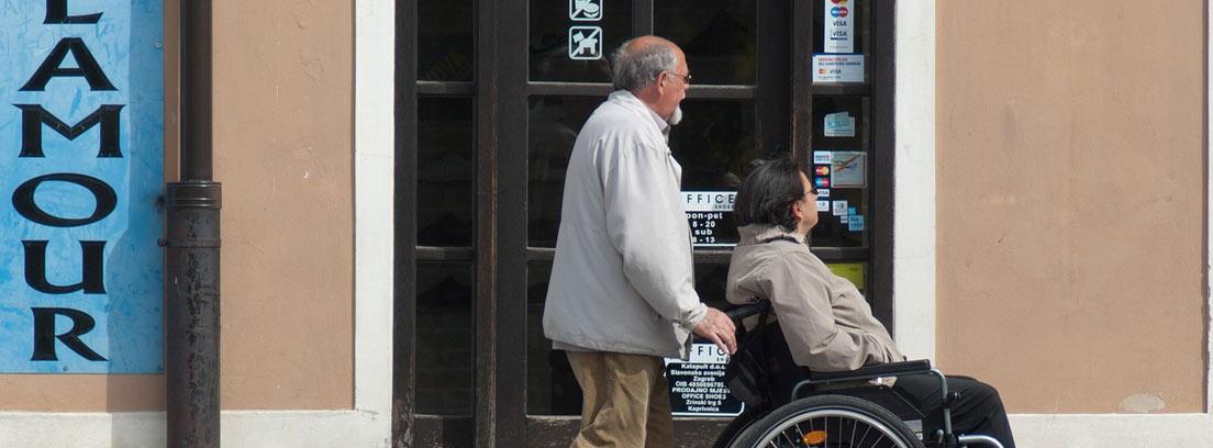 Hombre empuja silla de ruedas con una mujer sentada en ella