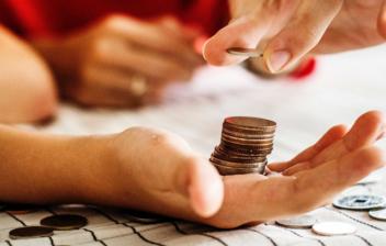 Mano deposita sobre otra con columna de monedas diferentes monedas