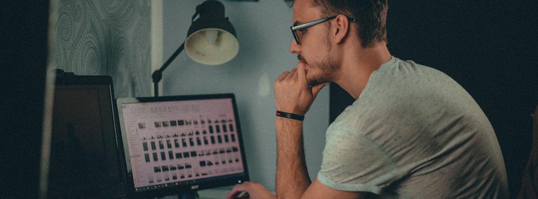 Hombre con gafas y manos sobre la barbilla mira ordenador