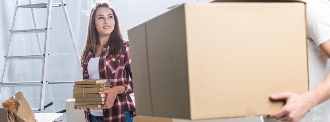 Mujer con libros atados y hombre con caja de mudanza