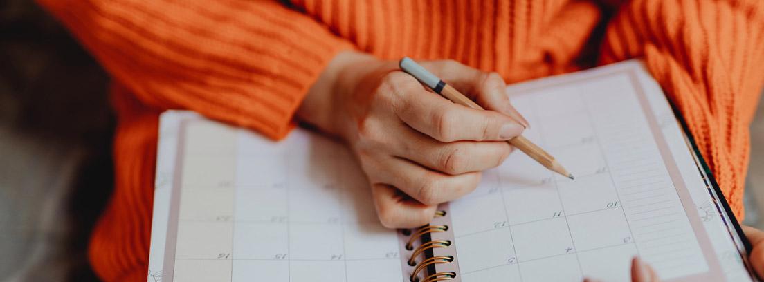 Persona con agenda de papel sobre las rodillas y con lápiz