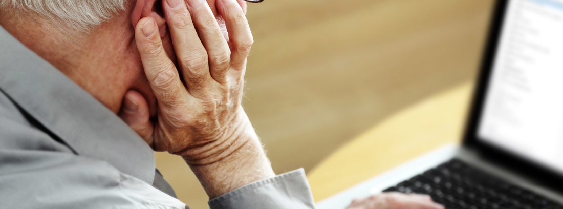 Hombre con pelo planco con mano apoyada en la cara delante de ordenador