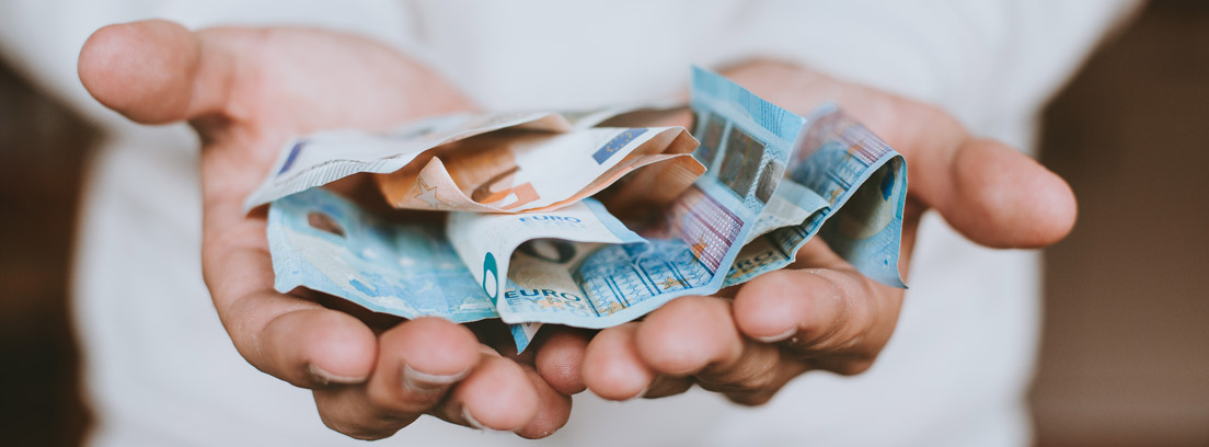 Billetes de euros y monedas sobre las manos de una persona