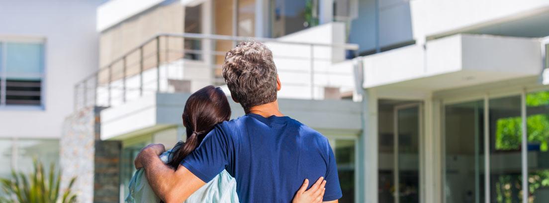 Pareja de espaldas abrazándose mirando una casa