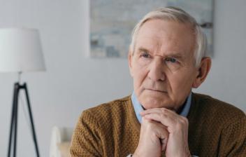 Hombre con pelo blanco y gesto pensativo con codos sobre mesa