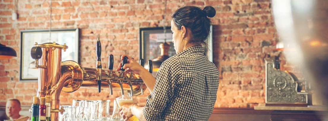Mujer de espaldas detrás de una barra de bar sirviendo una cerveza en un vaso