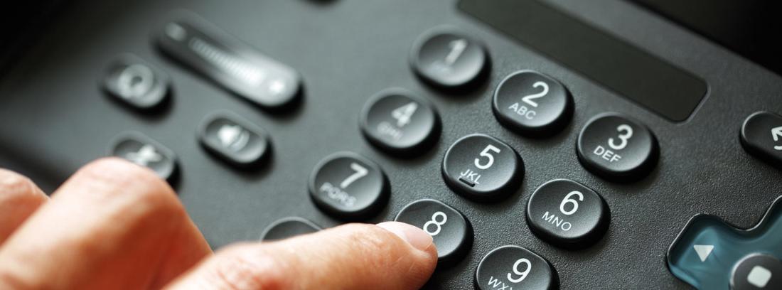 Mano marcando en un teléfono