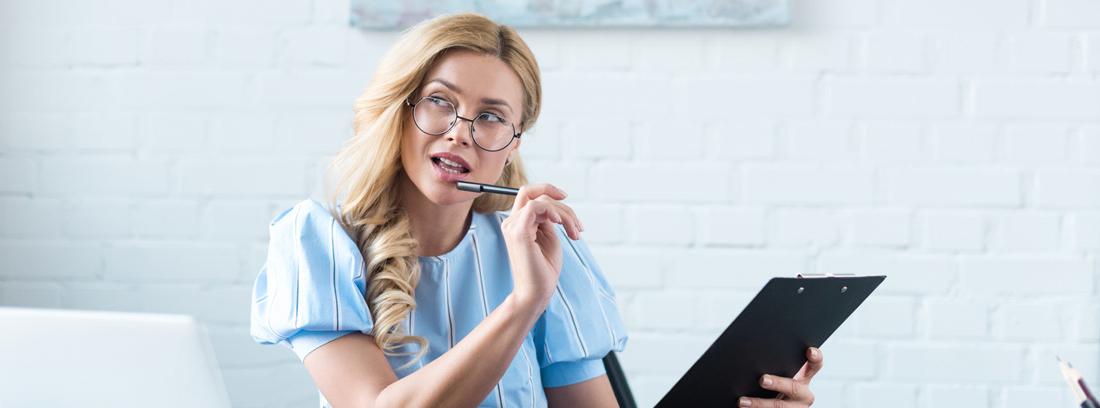 Mujer con gesto de duda con gafas, carpeta y bolígrafo