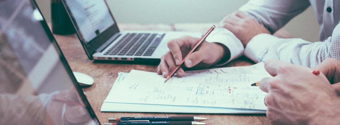 Manos en mesa con lápices señalando sobre papeles con cuentas y junto a ordenadores