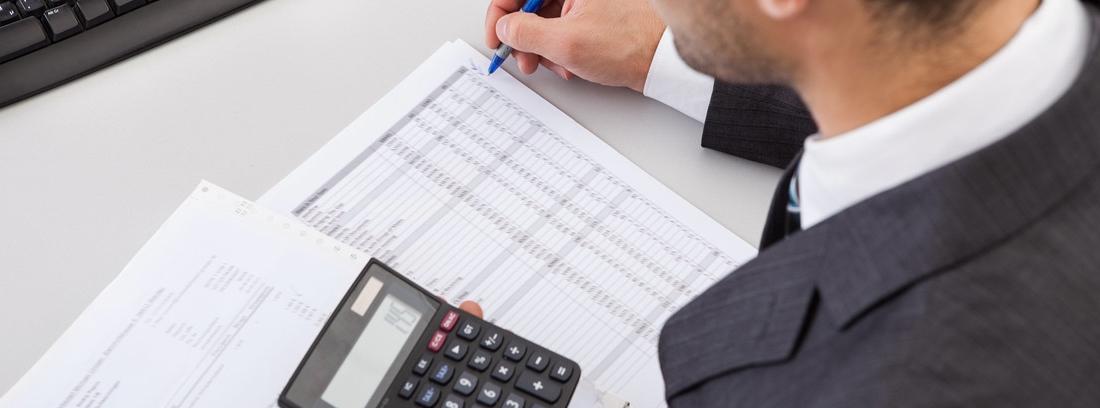 Hombre con calculadora y bolígrafo sobre facturas de papel