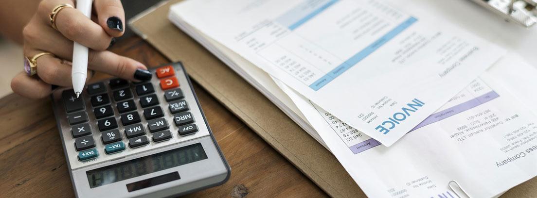 Mano sobre calculadora con bolígrafo y al lado de facturas de papel