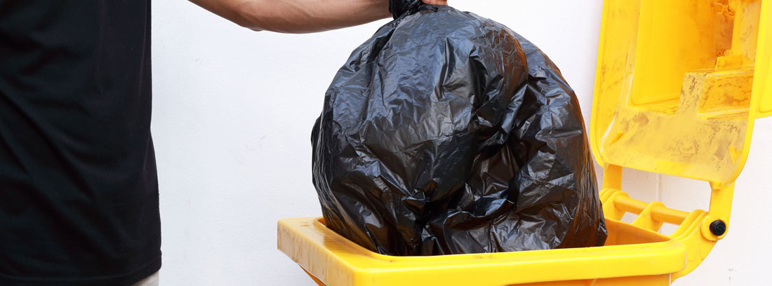 Hombre tirando una bolsa de basura a un contenedor amarillo