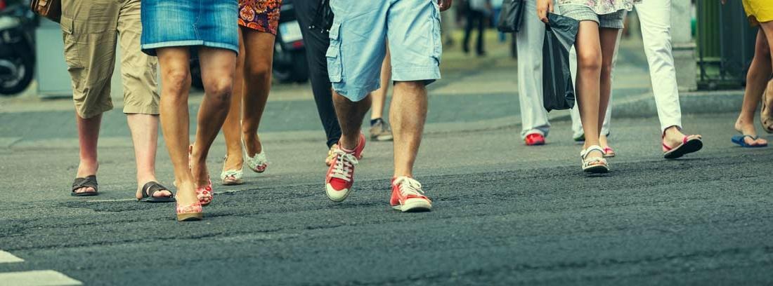 Vista parcial de las piernas de un grupo de personas cruzando una calle